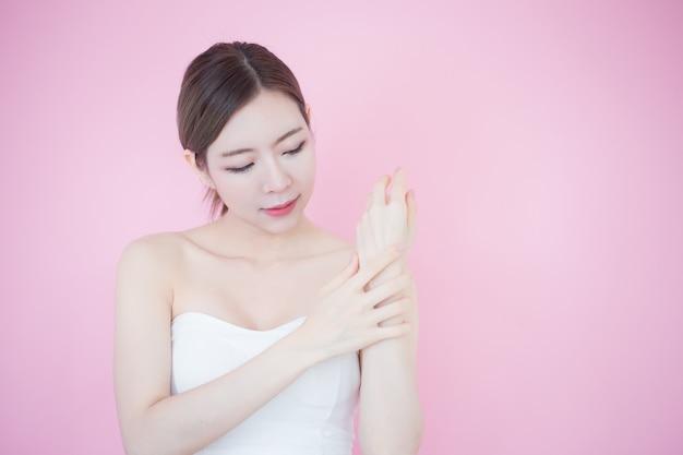 Gros plan belle jeune femme à la peau douce et propre avec fond rose