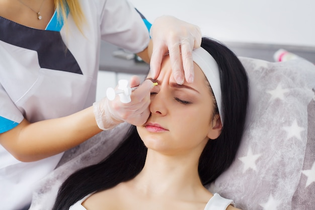 Gros plan de belle jeune femme reçoit une injection dans la zone des yeux et des lèvres de l'esthéticienne. préservation du concept de beauté