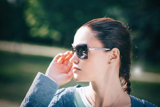 Gros plan.belle jeune femme regardant à travers des lunettes de soleil