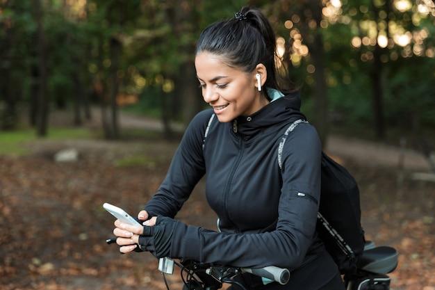 Gros plan d'une belle jeune femme de remise en forme à cheval sur un vélo dans le parc, écouter de la musique avec des écouteurs, tenant un téléphone mobile