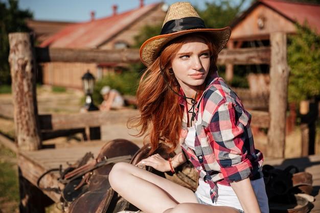 Gros plan de la belle jeune femme rousse cowgirl au chapeau