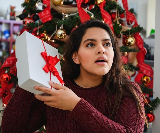 Gros plan d'une belle jeune femme tenant un cadeau de noël