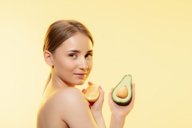 Gros plan de la belle jeune femme avec des tranches de citron sur fond jaune. concept de cosmétiques, maquillage, traitement naturel et écologique, soins de la peau. peau brillante et saine, mode, soins de santé.