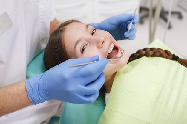 Gros plan d'une belle jeune fille souriante à la caméra pendant l'examen dentaire