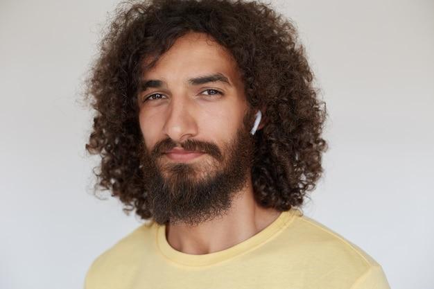 Gros plan de la belle jeune homme bouclé aux cheveux noirs avec de charmants yeux bruns à la recherche positive avec un sourire clair, portant une barbe luxuriante et écoutant de la musique dans ses écouteurs
