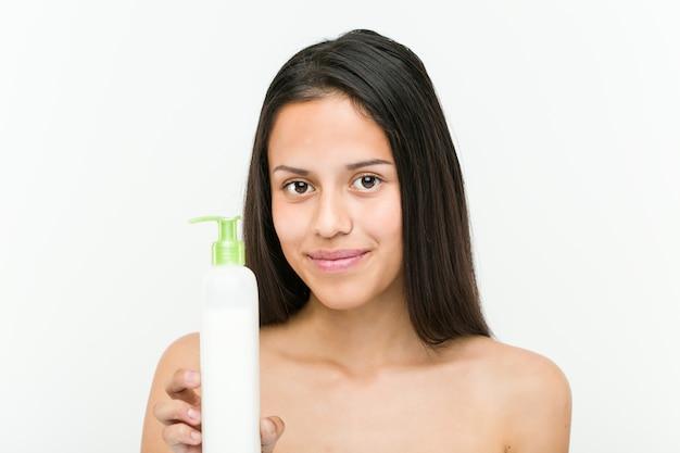 Gros plan d'une belle et naturelle jeune femme hispanique tenant une bouteille de crème hydratante