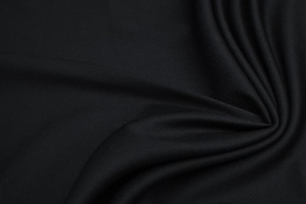 Gros plan de la belle texture de tissu noir froissé.