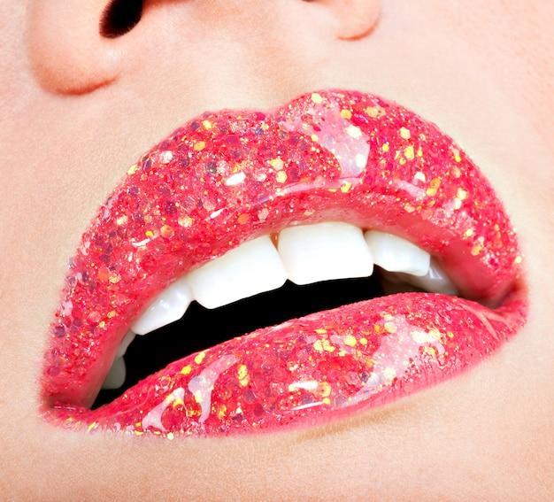 Gros plan de belles lèvres féminines avec rouge à lèvres brillant rouge brillant