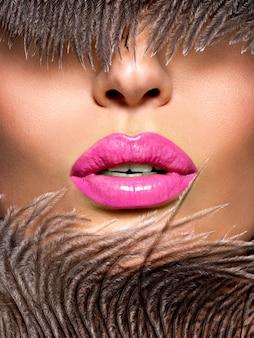 Gros plan belles lèvres féminines avec rouge à lèvres rose. maquillage brillant à la mode glamour.
