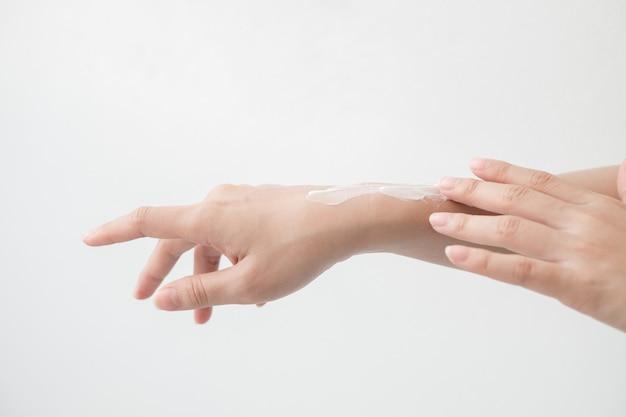 Gros plan de belles mains féminines tenant par la main et appliquant une crème hydratante