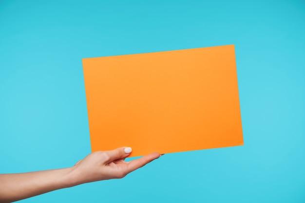 Gros plan sur de belles mains tenant une feuille de papier vierge