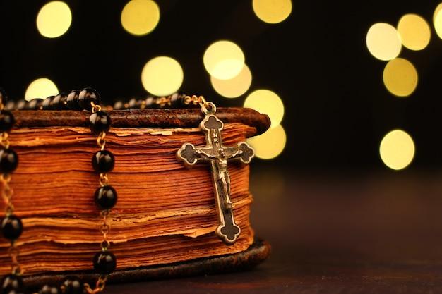Gros plan de la bible et du chapelet avec des lumières bokeh