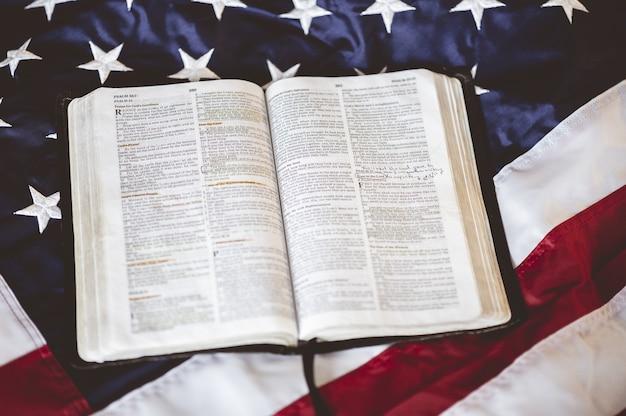 Gros plan de la bible ouverte dans les pages mises sur le drapeau américain - parfait pour prier le concept