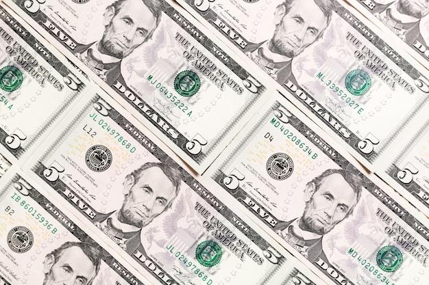 Gros plan sur des billets de 5 dollars en arrière-plan. modèle de dollars américains. vue de dessus du concept d'entreprise.