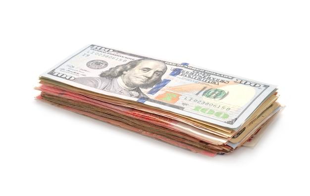 Gros plan de billets en dollars isolés empilant sur fond blanc.