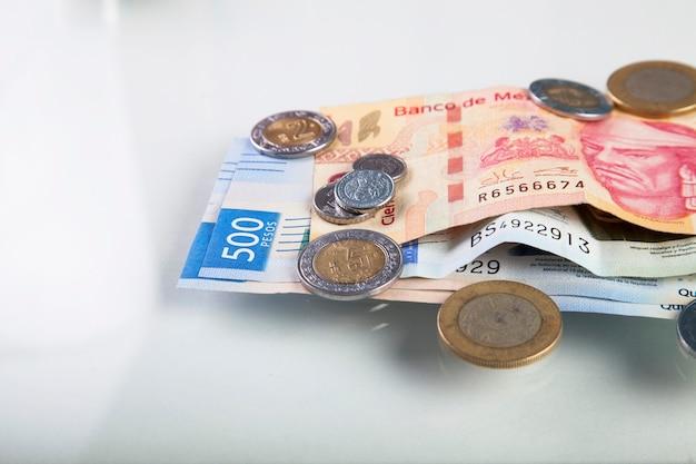Gros plan sur les billets et pièces de monnaie en peso mexicain