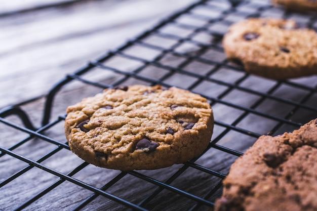 Gros plan de biscuits aux pépites de chocolat maison fraîchement cuits sur un filet de four