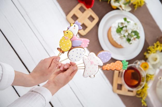 Gros plan de biscuits de pain d'épice de pâques lumineux sur des bâtons. le concept de décoration pour les vacances de pâques.