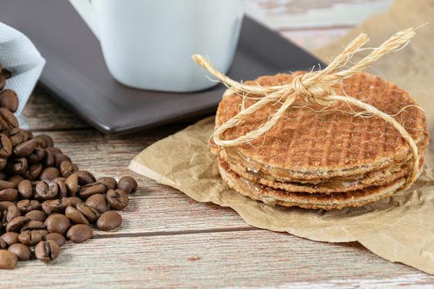 Gros plan des biscuits stroopwafel avec un arc en sisal à côté des grains de café.