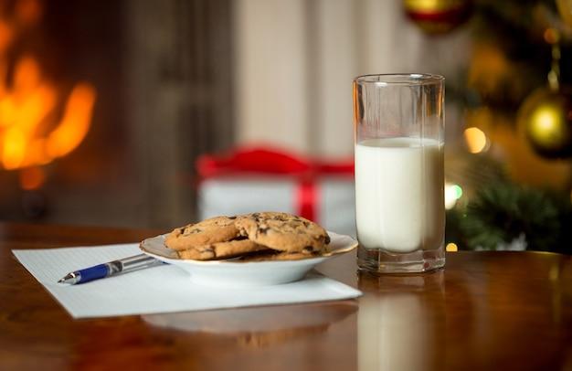 Gros plan sur des biscuits, un verre de lait et une lettre pour le père noël sur une table à côté d'une cheminée en feu et d'un arbre de noël
