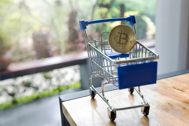 Gros plan de bitcoins d'or dans les chariots miniatures