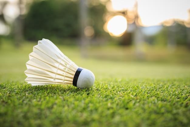 Gros plan blanc shuttlecock pour le badminton sur l'herbe verte