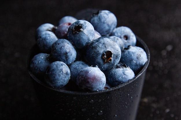 Gros plan de bleuets dans un bol noir avec fond sombre
