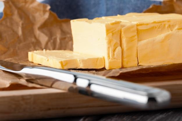 Gros plan sur le bloc de beurre coupé avec un couteau