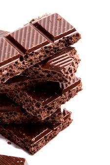 Gros plan de blocs de chocolat noir sur fond blanc