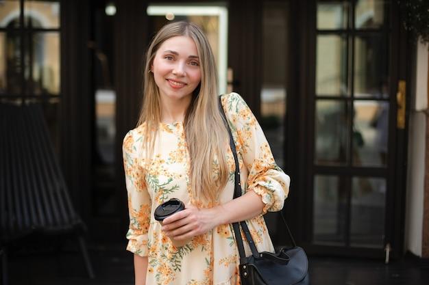 Gros plan d'une blonde heureuse de femme caucasienne dans une robe avec un sac noir buvant du café à emporter sur un fond de verre noir dans la ville