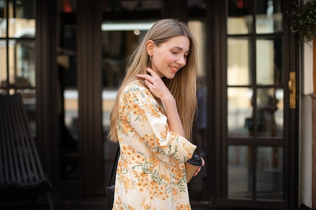Gros plan sur une blonde heureuse de femme caucasienne vêtue d'une robe qui redresse ses cheveux et regarde vers le bas en train de boire du café à emporter sur fond de verre noir dans la ville