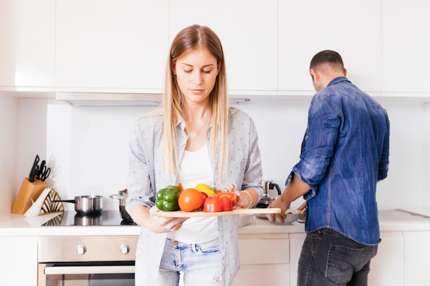 Gros plan d'une blonde jeune femme tenant des poivrons colorés à la main avec son mari à l'arrière-plan