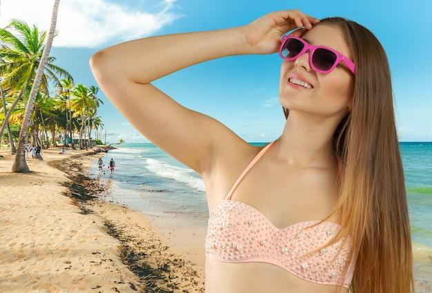Gros plan d'une blonde souriante à la recherche de la plage