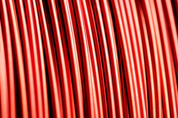 Gros plan d'une bobine de fil de cuivre rouge dans la fabrication de pièces électriques