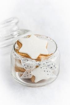 Gros plan d'un bocal en verre rempli de biscuits étoile faits maison de noël.