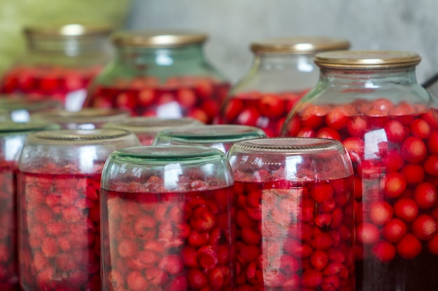 Gros plan des bocaux en verre avec des cerises douces juteuses rouges mûres recouvertes de couvercles métalliques à l'envers sur une plaque en bois. délicieuse cuisine traditionnelle maison, source de vitamines d'hiver.