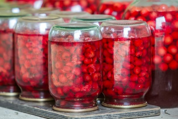 Gros plan des bocaux en verre avec des cerises douces juteuses rouges mûres recouvertes de couvercles métalliques à l'envers sur une plaque en bois.