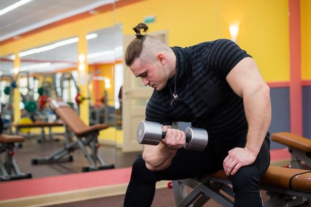 Gros plan d'un bodybuilder travaillant au gymnase
