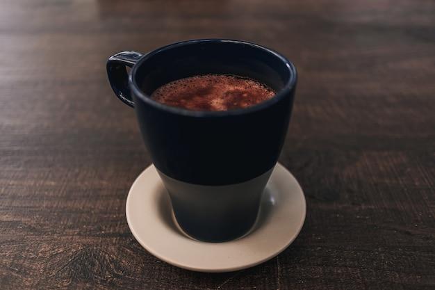 Gros plan sur une boisson chaude au cacao dans une tasse bleue sur une table en bois