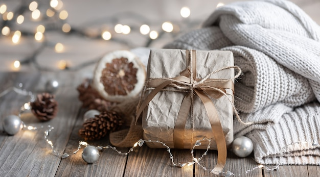 Gros plan sur une boîte-cadeau, détails d'un décor de noël festif et éléments tricotés sur un arrière-plan flou avec bokeh.