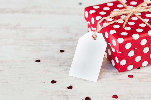 Gros plan d'une boîte de cadeau en pointillé rouge sur bois blanc, fond. note vide