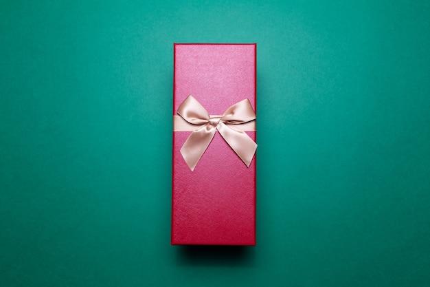 Gros plan d'une boîte cadeau rouge avec un arc d'or sur la surface de couleur verte