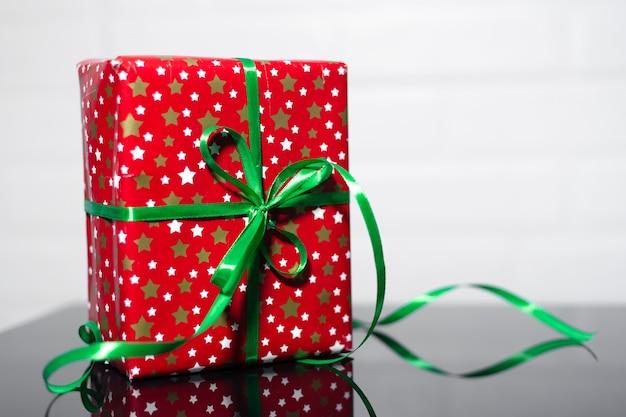 Gros plan, de, boîte cadeau rouge, à, arc vert, sur, verre noir