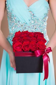 Gros plan sur une boîte en carton avec des fleurs roses rouges dans les mains des femmes
