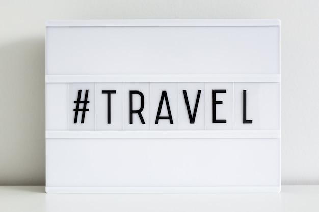 Gros plan sur une boîte à lumière rétro avec une étiquette de hachage de voyage écrite
