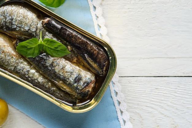 Gros plan sur une boîte de sardines à l'huile, avec du basilic et des feuilles d'olivier sur une serviette bleue et un espace de copie