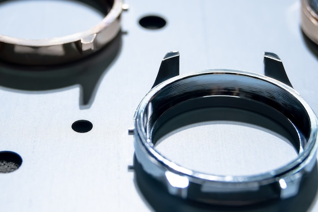 Gros plan sur un boîtier de montre en acier inoxydable brillant réchauffé à l'intérieur de la machine de dépôt en phase vapeur, revêtement pvd pour durcir le cadre de la montre-bracelet, augmenter la durabilité et acquérir un look luxueux en titane doré