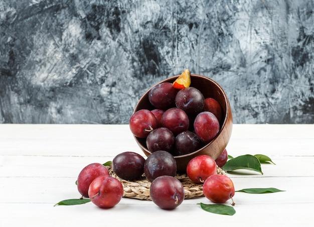 Gros plan un bol de prunes sur napperon en osier sur planche de bois blanc et fond de marbre bleu foncé. horizontal
