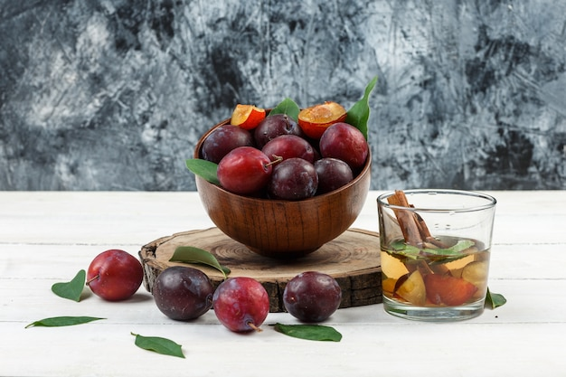 Gros plan un bol de prunes sur planche de bois avec de l'eau de désintoxication et des feuilles sur planche de bois blanc et fond de marbre bleu foncé. horizontal