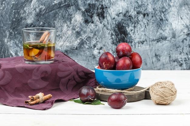 Gros plan un bol de prunes sur une planche à découper avec de l'eau d'écoute, de cannelle et de désintoxication sur une planche de bois blanche et fond de marbre bleu foncé. espace libre vertical pour votre texte